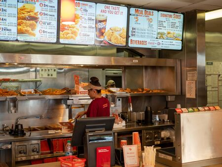 Woman working behind counter at Popeyes Fried Chicken location