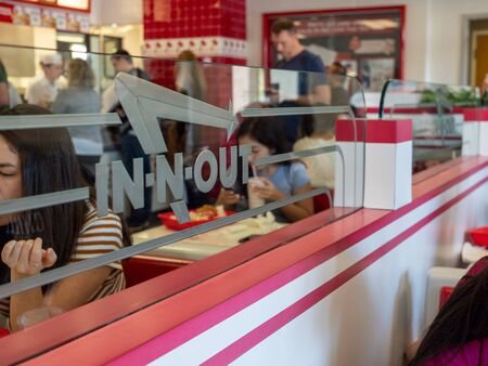 Diners eating at In-N-Out Burger location behind logo on glass divider 報道画像