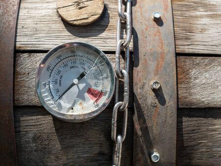 Broken thermometer gauge and chain sitting on top of smoker grill bbq