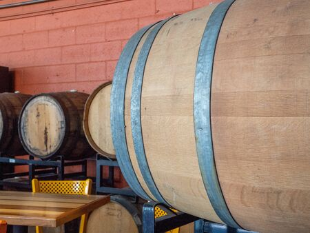 Barrels lining the corner of a winery or brewery with dining tables