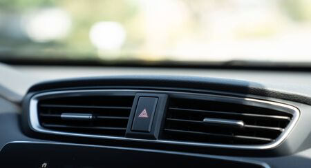 Emergency light button on dashboard of car between air vents Stock Photo