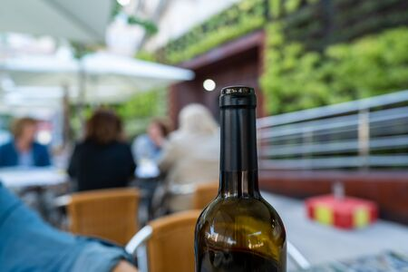 Open bottle of red wine at an outdoor restaurant with patrons