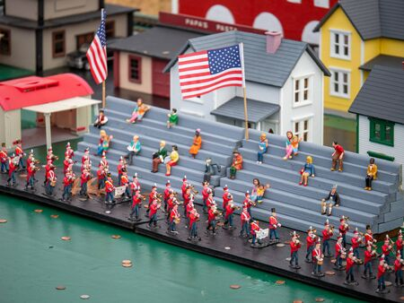 Miniature figurines marching band in parade with on lookers with US flag Imagens