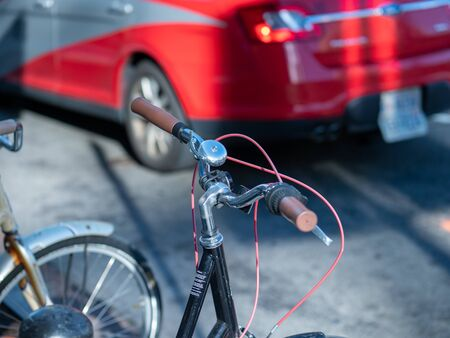 Close up of bike handlebars and bell parked on street