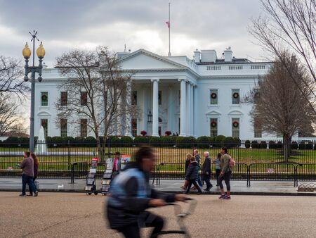 Man on bike races past White House lawn on overcast day