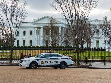 Police car and officers guarding gate of White House Editorial