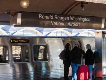 Ronald Reagan Washington National Airport wmata meto train subway stop with train moving and passengers waiting to board