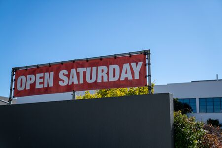 Open Saturday sign hanging on top of store building on sunny day