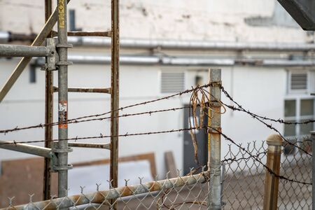 Barbed wire and dirty string on top of rusty fence blocking entrance to a building Stock Photo