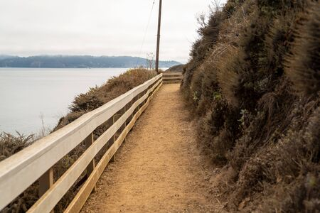 Dirt walking path with white rail overlooking cliff a body of water