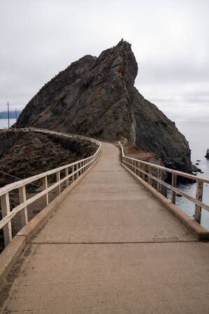 Concrete foot bridge with white wooden handrails leading to a cliff above the sea with tourists in background