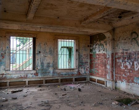 Abandoned prison jail building complex with graffiti and broken foundation