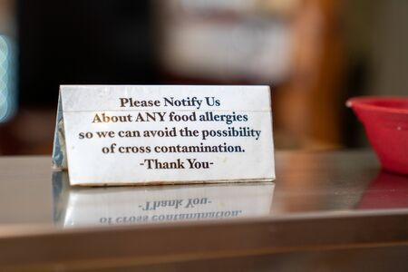 Food allergy cross contamination warning placard notice sitting on stable at restaurant