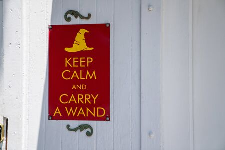Keep calm and carry a wand gag humor sign hanging on wall Imagens