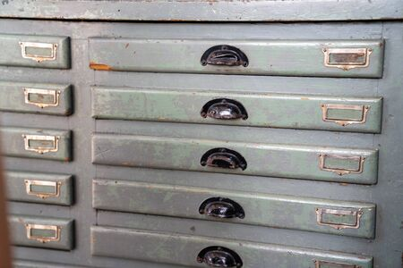 Wooden grey filing cabinet drawer with some empty label slots Imagens
