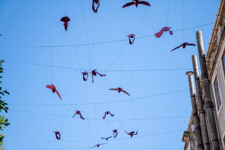 Decorative paper birds hanging on strings high on buildings against sky