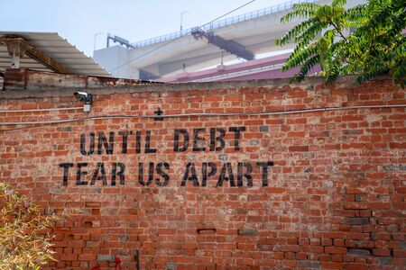 Until debt tear us apart message spray painted political protest message on brick wall