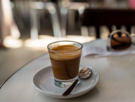 Expresso coffee in small glass with spoon on white table in a restaurant