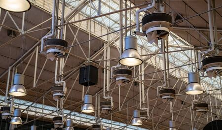 Various industrial lights hung high in bright modern warehouse