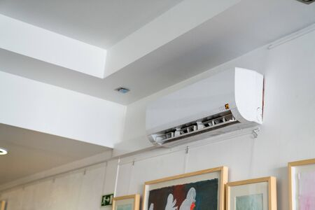 Air conditioning unit mounted high on wall near ceiling inside building