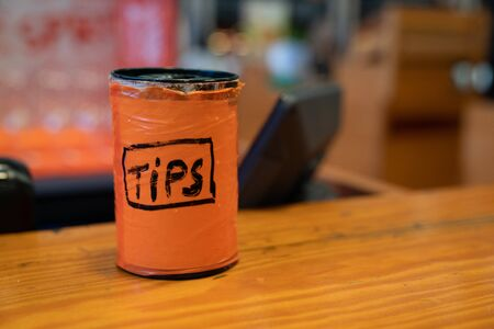 Orange tips jar sitting on bar countertop for the bartender and drinks