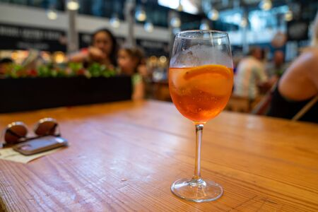 Orange spritz cocktail in wine glass sitting on a wooden table Imagens