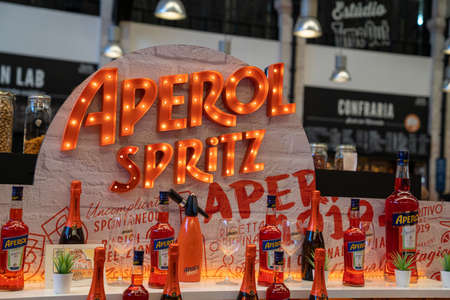 Aperol Spritz orange neon logo and display at custom bar at Time Out Market Lisbon Editorial