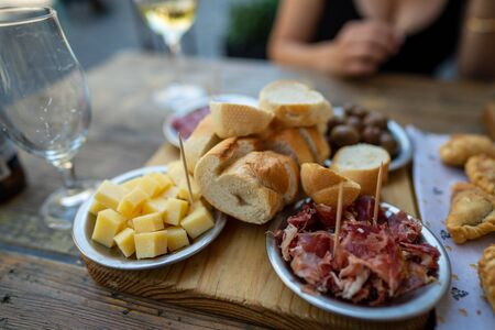 Charcuterie selection with cured prosciutto meats, cheese, olives, and drinks