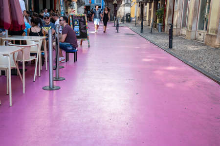 Tourist walking and dining in Pink Street district in Lisbon