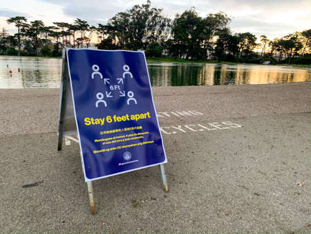 San Francisco, California March 23, 2020: Stay 6 feet apart social distancing guidelines for coronavirus COVID-19 in multiple languages and diagram in Golden Gate Park in San Francisco on lake bike path