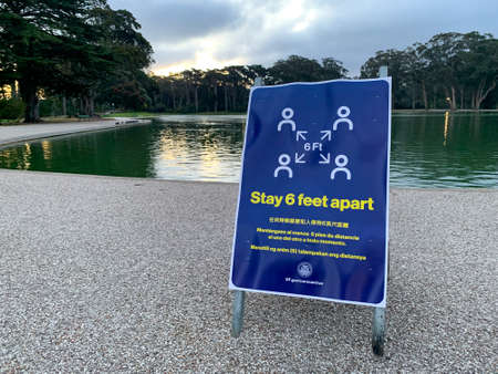 San Francisco, California March 23, 2020: Stay 6 feet apart social distancing guidelines for coronavirus COVID-19 in multiple languages and logo in Golden Gate Park in San Francisco in front of lake Editorial