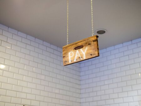 Wooden pay sign hanging over cash register payment area in cafe Banco de Imagens