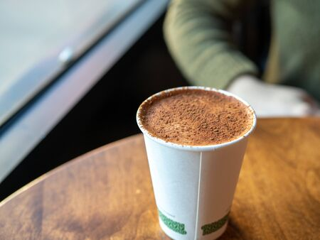 Coffee latte covered in cocoa powder in compostable cup on table in cafe
