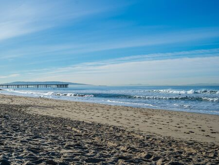 Beach with waves crashing on sunny morning with a dock pier