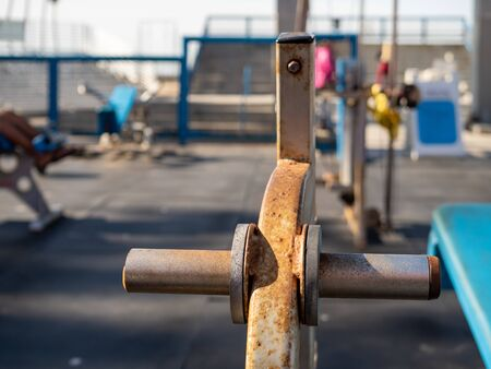 Close up of rusted weight rack in outdoor gym