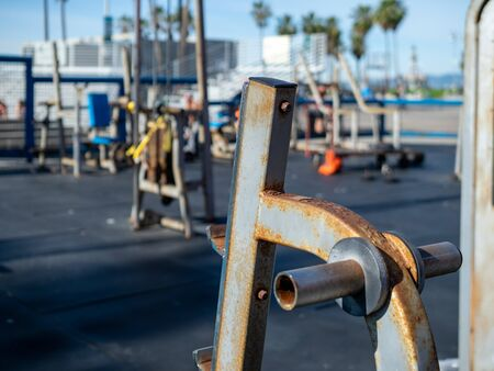 Rusted outdoor weight rack empty at public gym with workout equipment in background