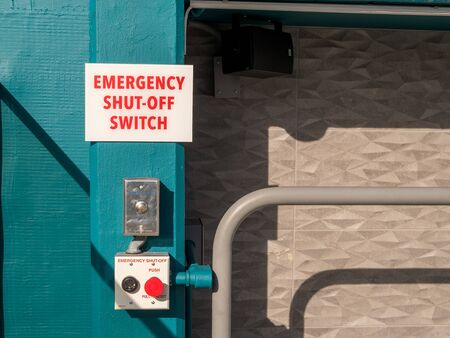 Emergency shut-off switch sign and button outside of pool