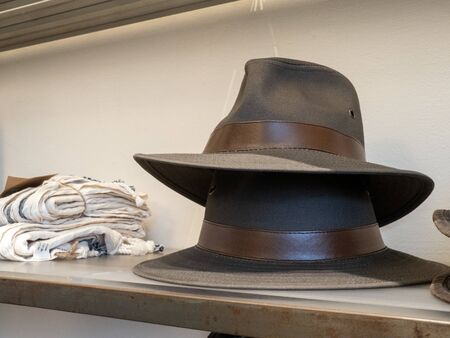 Stack of two fedora hats on display in department store clothes section