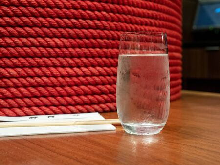 Glass of water next to decorative column covered in red string in Asian restaurant