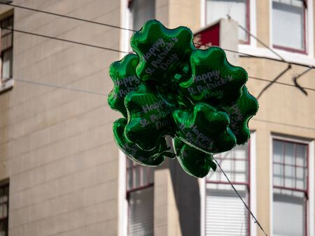 Bunch of happy St Patrick s Day green shamrock balloons floating in city