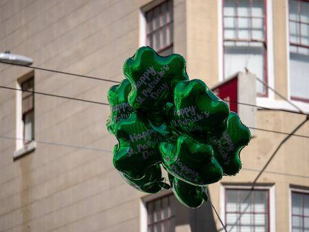 Festive happy St Patrick s Day green shamrock balloons floating in urban setting
