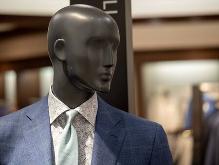 Male mannequin figure posing with colorful suit in department store