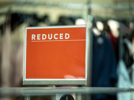 Orange reduced price sale sign on clothing rack in department store Imagens
