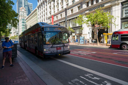 Muni bus Fulton line 5 on moving past person on Market Street shopping district