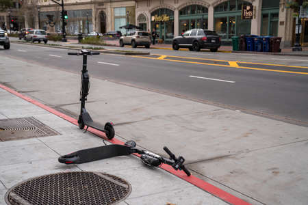 Bird electric scooters resting haphazardly on sidewalk and bus lane Editorial