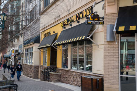 Buffalo Wild Wings restaurant location on street with people walking by