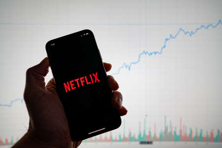 Netflix app on phone with white financial stock chart with price rising upward positive in background