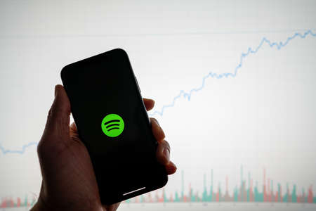 Spotify app on phone with white financial stock chart with price rising upward positive in background 新闻类图片