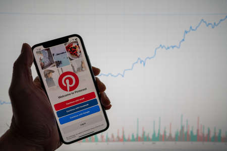 Pinterest app on phone with white financial stock chart with price rising upward positive in background
