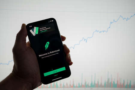 San Francisco, California February 09, 2020: Robinhood app on phone with white financial stock chart with price rising upward positive in background Editorial